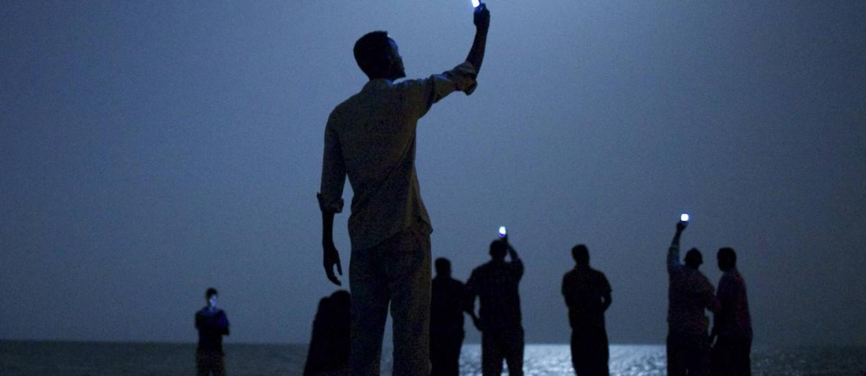 Migrantes africanos na costa do Djibouti buscam sinal para ligar para parentes: foto de John Stanmeyer Foto: John Stanmeyer / Divulgação