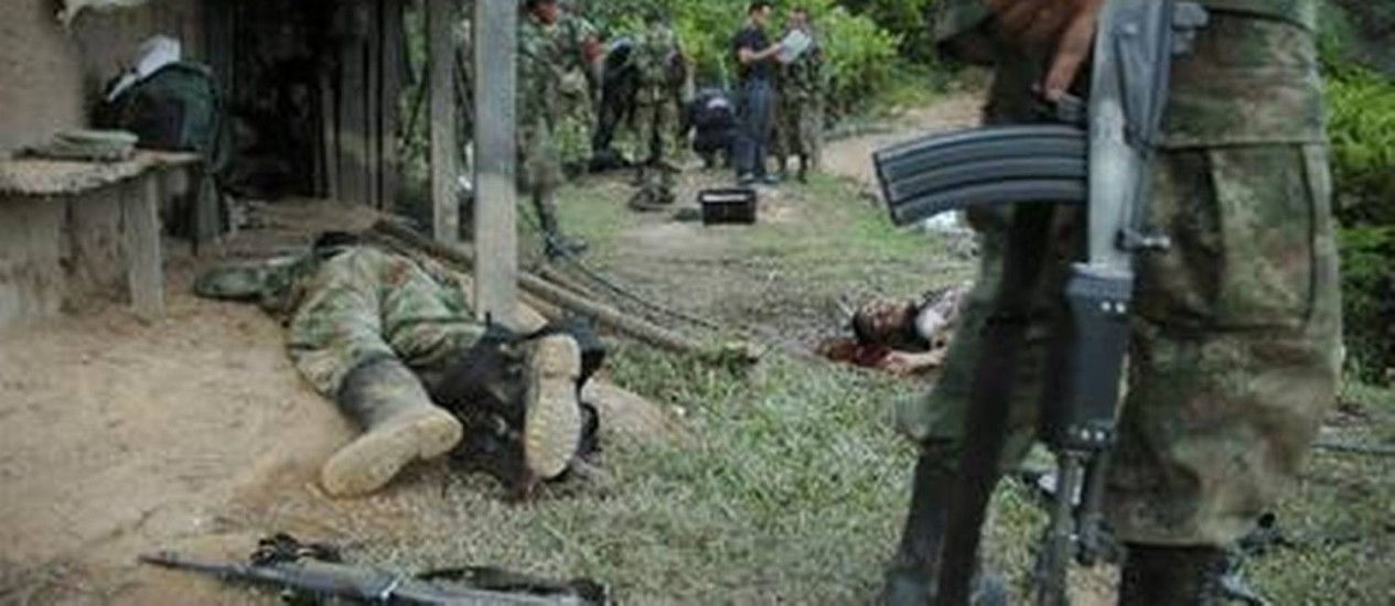 Soldado para ao lado do corpo de um membro do ELN em San Isidro Foto: AP/2008