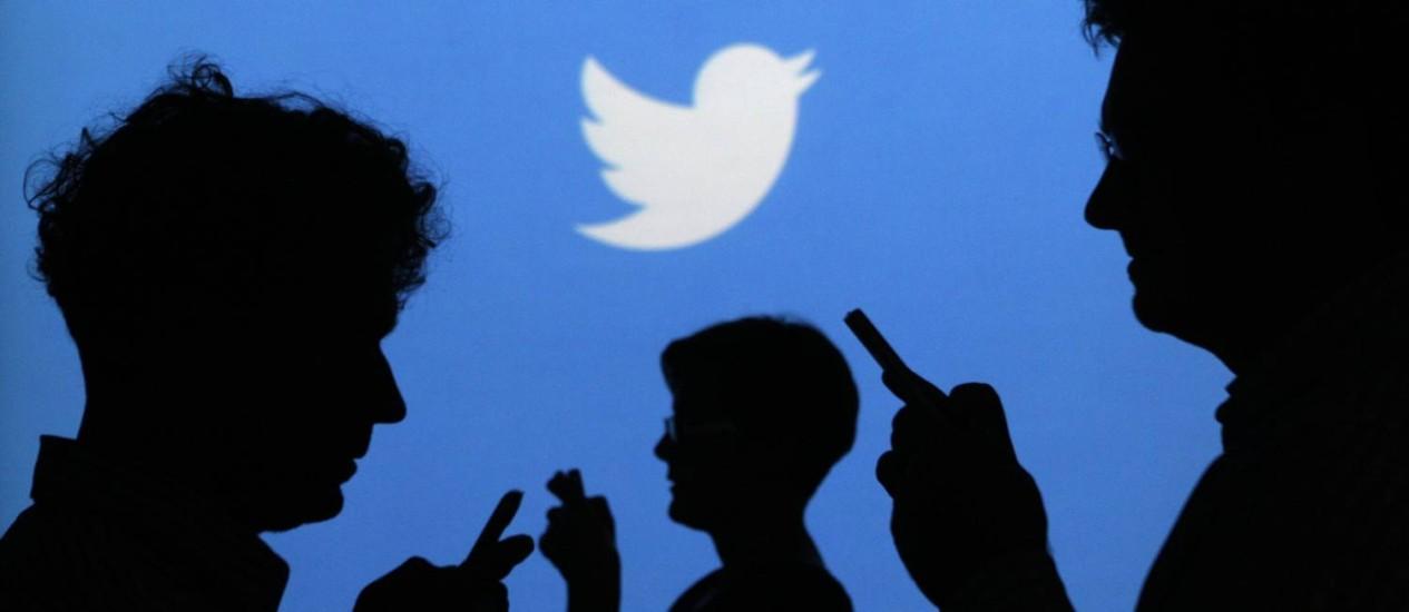 Pessoas usam seus celulares com o logo do Twitter ao fundo Foto: KACPER PEMPEL / REUTERS