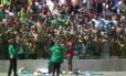 Samuel Eto'o autografa camisas jogadas por torcedores em Vitória