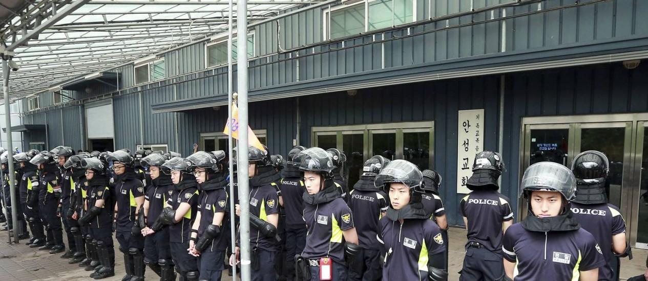 Policiais sul-coreanos montam guarda em frente ao portão principal de propriedade da Igreja evangélica batista em Anseong Foto: YONHAP / REUTERS