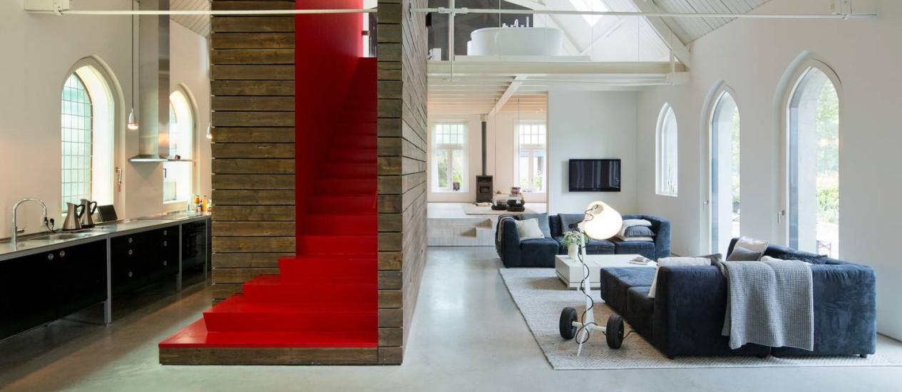 Uma escada vermelha divide os cômodos da casa e quebra o branco predominante Foto: Andreas Meichsner/NYT