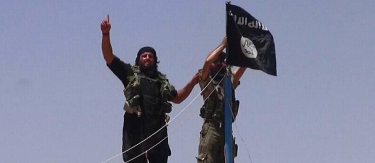 Imagem divulgada no Twitter mostra um membro do Isis hasteando uma bandeira na província iraquiana de Nínive Foto: - / AFP
