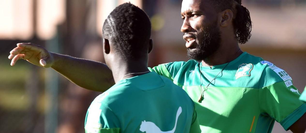 O atacante Didier Drogba conversa com companheiro no treinamento em Águas de Lindoia Foto: ISSOUF SANOGO/AFP