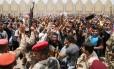 Homens iraquianos entoam palavras de ordem contra o Estado Islâmico do Iraque e da Síria (Isis) do lado de fora do principal centro de recrutamento de voluntários do Exército para o serviço militar em Bagdá