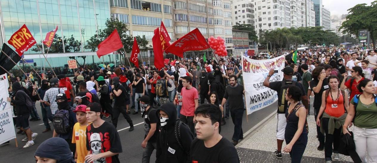 Manifestantes contra a Copa caminham na orla de Copacabana Foto: Domingos Peixoto / Agência O Globo