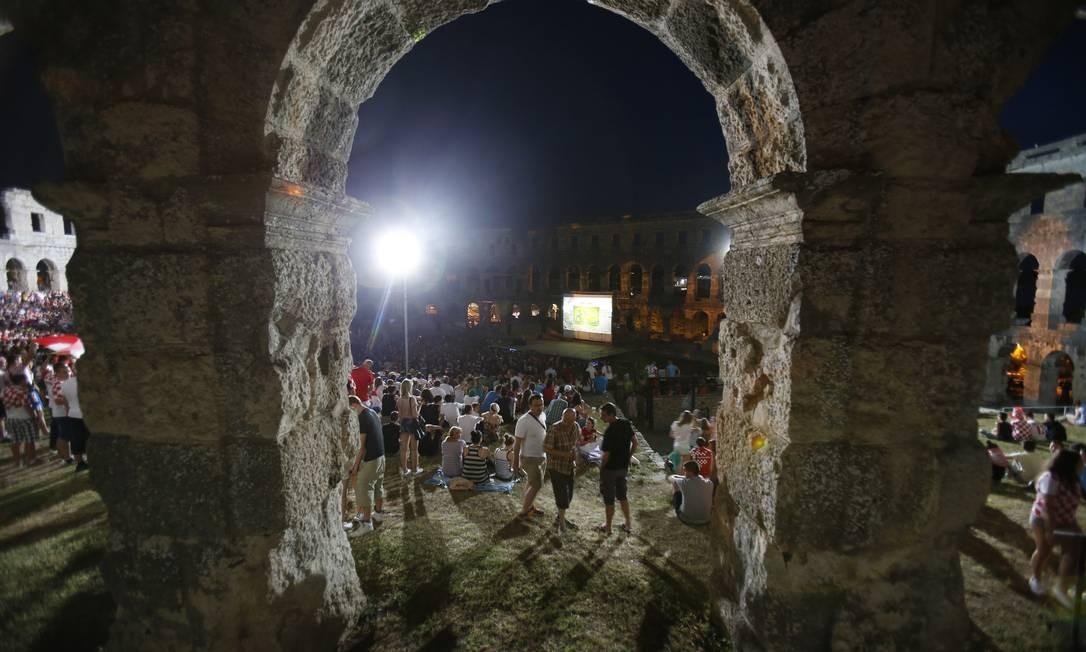 Já em Pula, na Croácia, torcedores assistem à estreia da seleção nacional contra o Brasil em ruínas de anfiteatro romano. Darko Bandic / AP