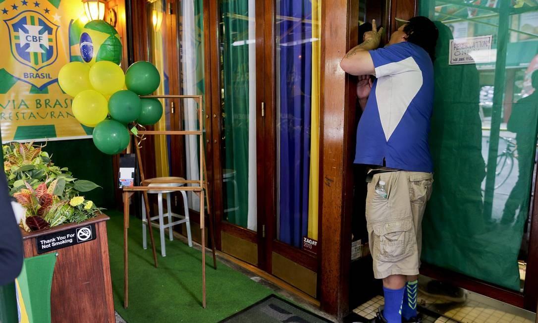 Em Nova Iorque, torcedor espia janela de restaurante brasileiro, totalmente lotado, em dia de partida de estreia da Copa contra a Croácia. Julie Jacobson / AP