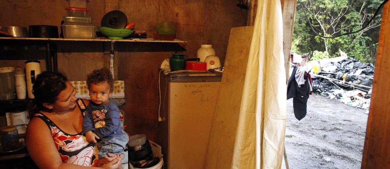 Angélica Costa, como filho no colo, vive em situação precária no Caju: desempregada, ela vive em barraco mínimo que não tem sequer banheiro Foto: Antonio Scorza / Agência O Globo