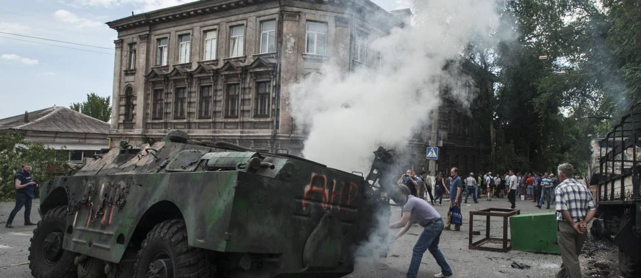 Moradores observam veículo militar em chamas após batalha entre tropas ucranianas e combatentes pró-russos em Mariupol Foto: Evgeniy Maloletka / AP