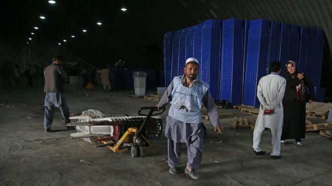 Homem carrega material eleitoral em Cabul Foto: Massoud Hossaini/AP