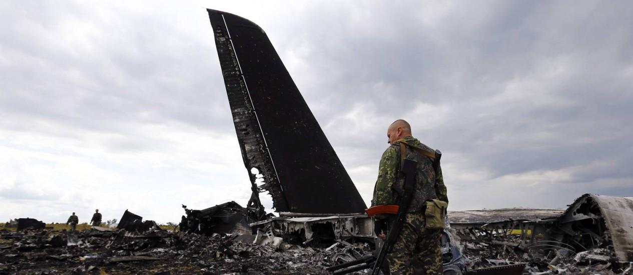 Separatista pró-Russia examina os restos do avião Il-76 das Forças Armadas ucranianas derrubado em Luhanksk Foto: SHAMIL ZHUMATOV / REUTERS