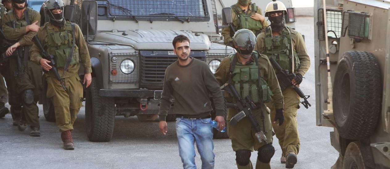 Soldados israelenses detêm um palestino suspeito durante as buscas pelos jovens desaparecidos na cidade de Hebron Foto: AFP/HAZEM BADER