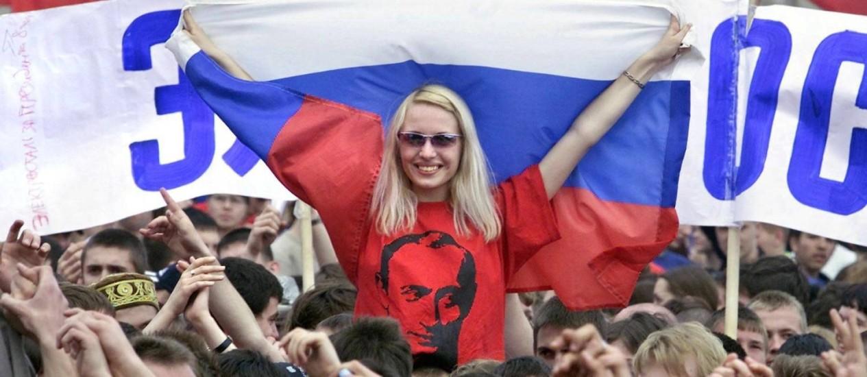 Jovem com camisa com o retrato do presidente Vladimir Putin participa de manifestação pró-governo em Moscou: histórias de glória dos tempos da União Soviética atraem a atenção da nova geração Foto: AFP/Yuri Kochetkov