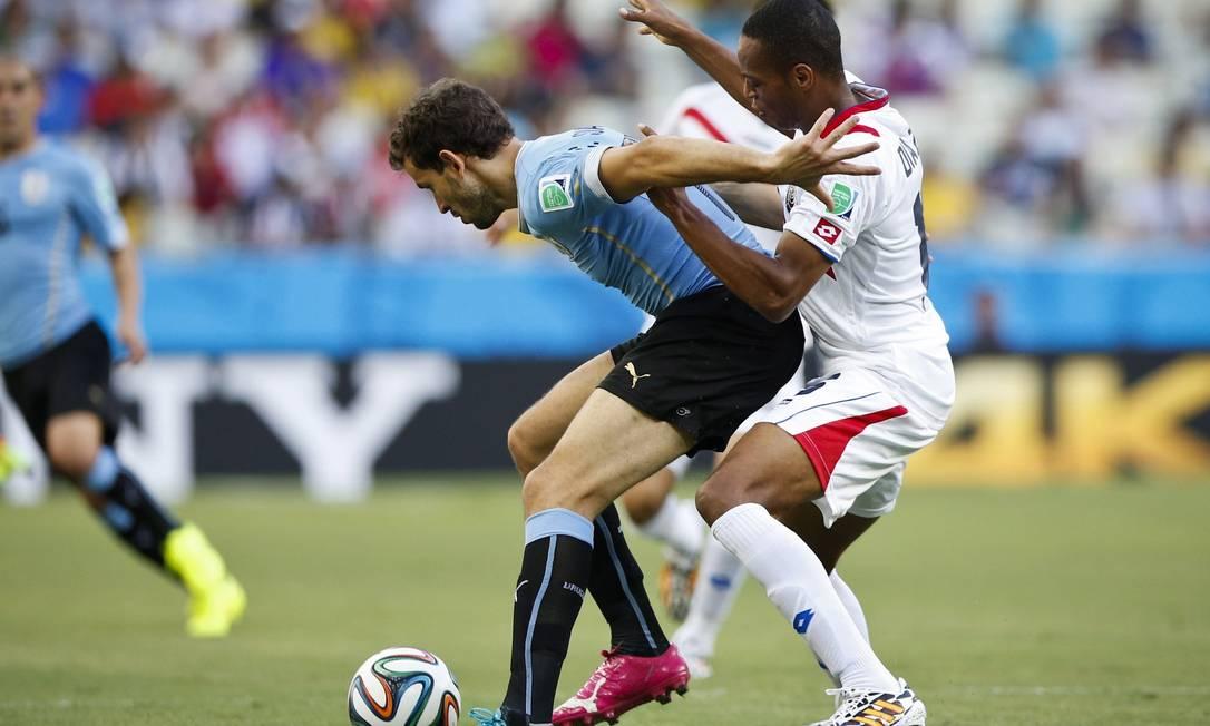 Na disputa de bola, o jogador uruguaio quase caiu no colo do atleta da Costa Rica Foto: Guito Moreto / Agência O Globo