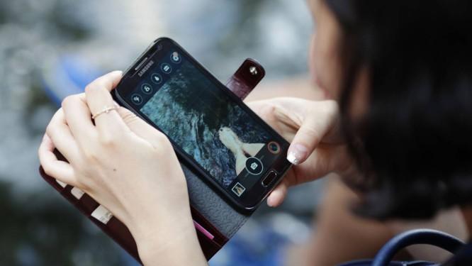 Mulher usa um celular da Samsung em Seul: tecnologia móvel cobre praticamente 100% da Coreia Foto: Woohae Cho / Bloomberg