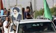 Civis iraquianos, um deles carregando uma foto do aiatolá Ali al-Sistani, o clérigo xiita mais influente do Iraque, se armam para enfrentar o Isis
