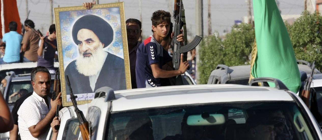 Civis iraquianos, um deles carregando uma foto do aiatolá Ali al-Sistani, o clérigo xiita mais influente do Iraque, se armam para enfrentar o Isis Foto: REUTERS