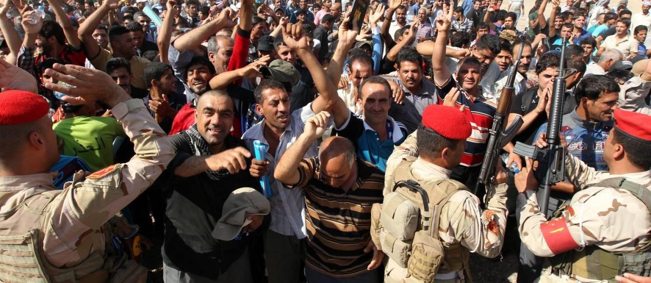 Homens iraquianos, que se voluntariaram para lutar contra os jihadistas, se reúnem em Bagdá antes de serem transportados para treinamento num acampamento de infantaria Foto: SABAH ARAR / AFP