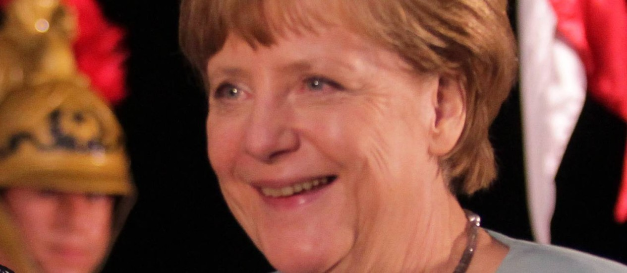 """Merkel recebeu um ramo de """"folha de Oxóssi"""" durante sua visita a uma escolinha de futebol em Salvador Foto: Ailton de Freitas / O Globo"""