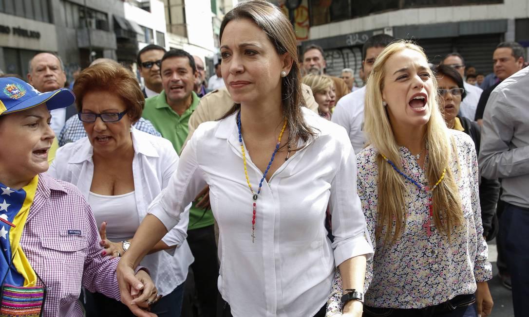 Maria Corina Machado (ao centro) caminha com Lilian Tintori (à direita), mulher do líder opositor preso Leopoldo López, até uma corte de Caracas Foto: Carlos Garcia Rawlins / REUTERS