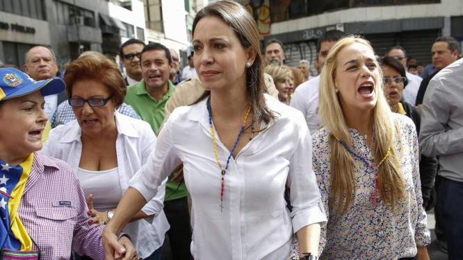 María Corina Machado (ao centro) caminha com Lilian Tintori (à direita), mulher do líder opositor preso Leopoldo López, até uma corte de Caracas Foto: Carlos Garcia Rawlins / REUTERS