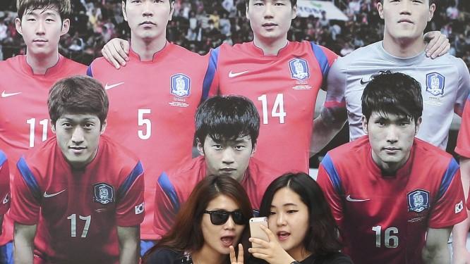 Torcedoras sul-coreanas entre as selfies e a imagem dos jogadores de sua seleção: equipe busca confiança Foto: Ahn Young-joon / AP