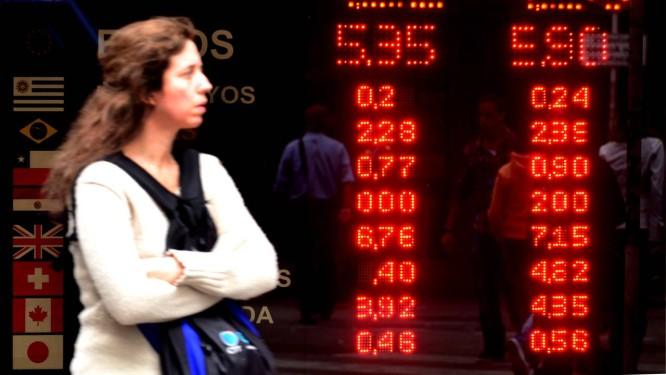 Mulher passa em frente a display da Bolsa de Buenos Aires, na Argentina Foto: Diego Giudice/Bloomberg