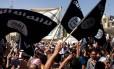 Manifestantes que apoiam o Estado Islâmico no Iraque e na Síria seguram bandeiras da al-Qaeda em frente à sede provincial do governo em Mossul, no Iraque