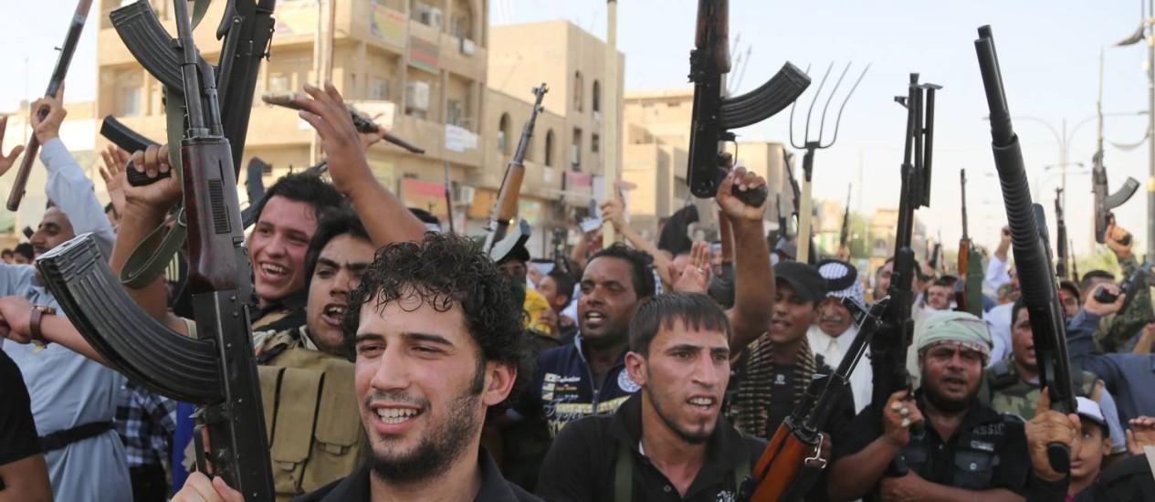Combatentes xiitas levantam armas e entoam palavras de ordem contra Isis em Bagdá Foto: Karim Kadim / AP