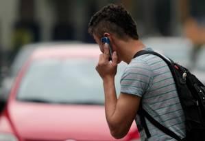 Rapaz fala ao celular: serviços de informação e comunicação subiram apenas 3,7%, bem inferior aos resultados de março (4,4%) e fevereiro (6,7%) Foto: Marcos Alves