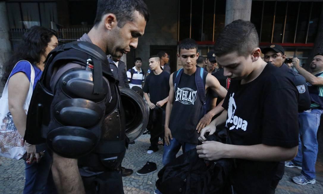 Manifestante mostra mochila e documento para policial Foto: Pablo Jacob / Agência O Globo