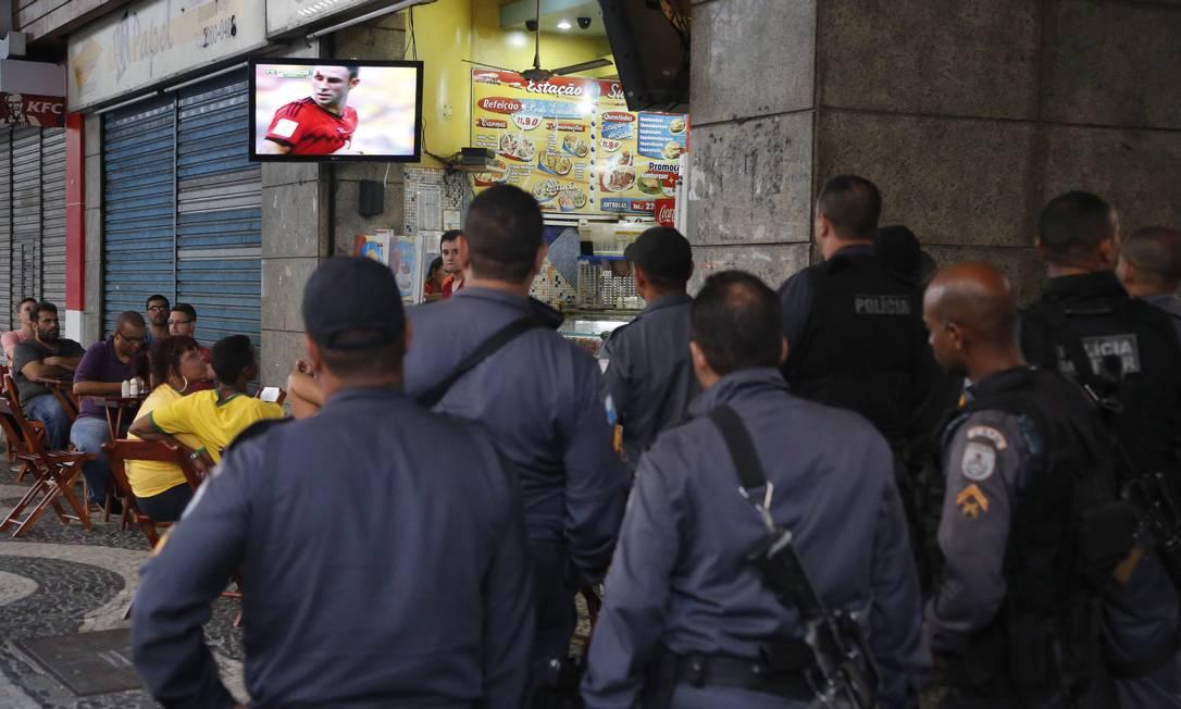 PMs assistem ao jogo em TV de bar na Candelária Foto: Pablo Jacob / Agência O Globo