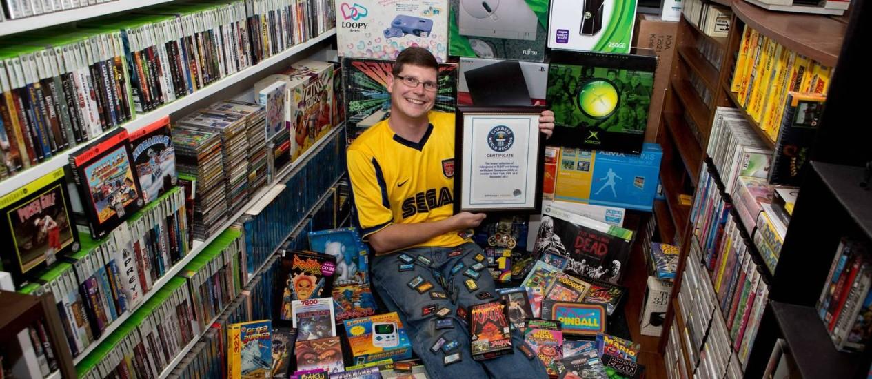 O americano Michael Thomasson com o seu certificado do Guinness e parte da sua coleção de videogames, vendida por mais de US$ 750 mil Foto: Brianna Blank / AP