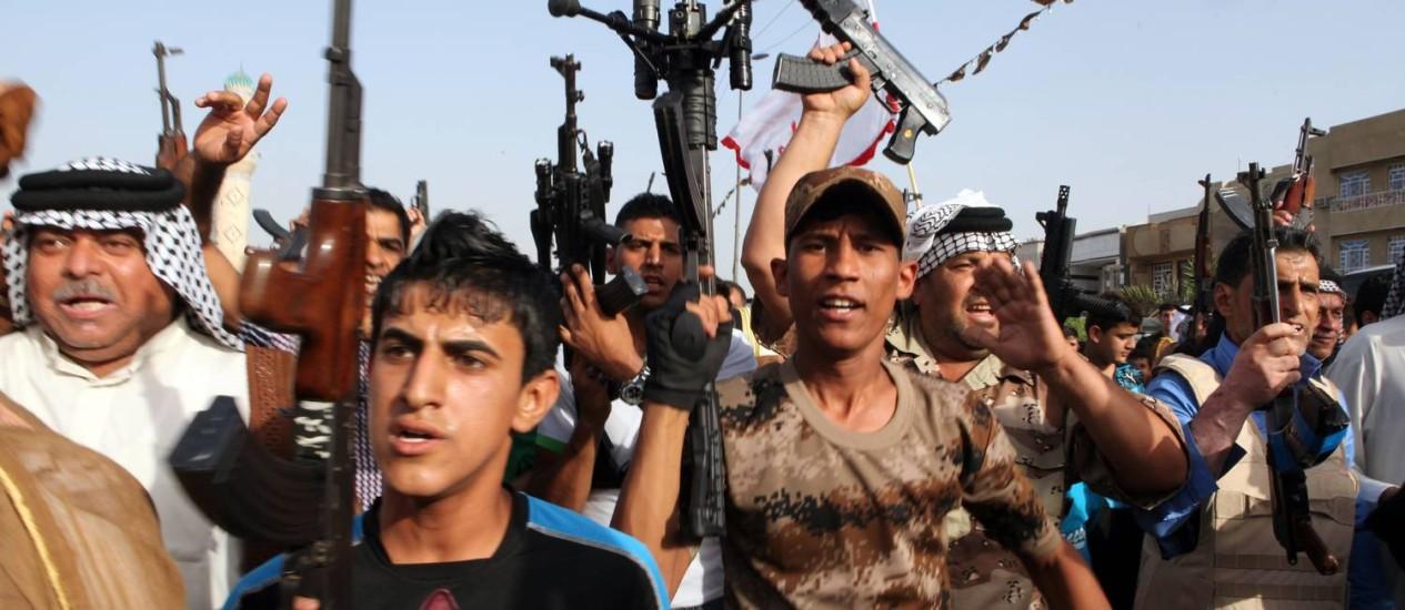 Xiitas iraquianos levantam suas armas demonstrando sua união às forças de segurança na luta contra jihadistas sunitas Foto: ALI AL-SAADI / AFP