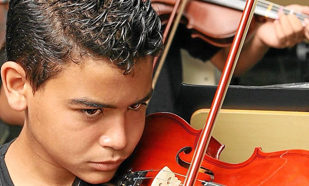 Jovem da Favela da Maré, no Rio, tocam violino: música amplia funções cognitivas Foto: / Laura Marques