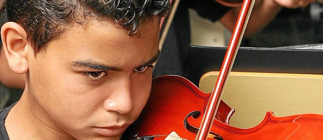 Jovem da Favela da Maré, no Rio, toca violino: música amplia funções cognitivas Foto: Laura Marques