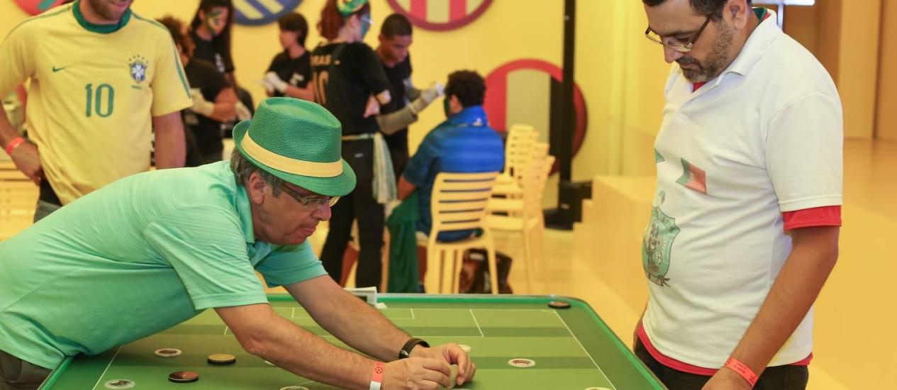 Os israelenses Miki e Jonathan aprendem com Jonas Kojala as regras do futebol de mesa. Já o grupo Bom Gosto comanda a animação do espaço nesta sexta-feira, a partir das 15h Foto: Marco Sobral / Divulgação
