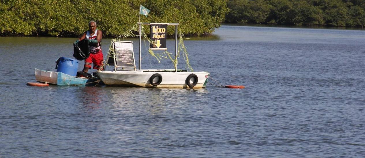 Meste Tuti e o barco com o qual recolhe lixo no Rio São João Foto: Cláudio Pacheco / Divulgação