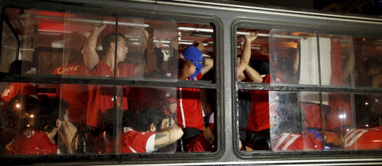 Torcedores chilenos, detidos após invadirem o Maracanã, foram levados da Cidade da Poícia para o Consulado, na Zona Sul, por ônibus da PM Foto: Hudson Pontes / Agência O Globo