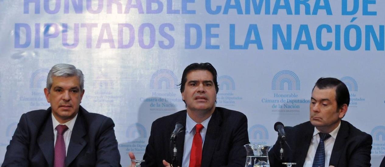 O chefe de gabinete argentino, Jorge Capitanich, ao lado do presidente do Senado em exercício, Gerardo Zamora (à direita) e o presidente da Câmara, Julian Dominguez Foto: CELESTE SALGUERO / AFP