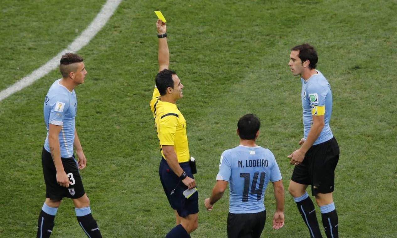 O uruguaio Diego Godin recebe o cartao amarelo do arbitro Carlos Velasco Carballo Foto: PAULO WHITAKER / REUTERS