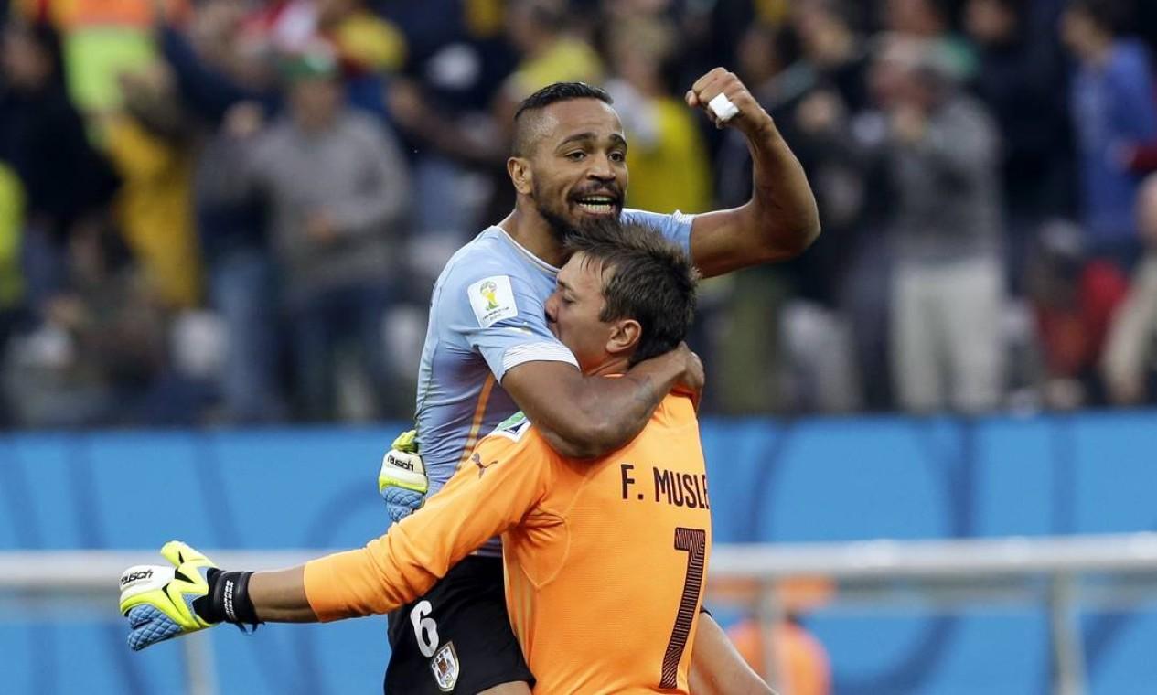 O goleiro Muslera e o zagueiro Alvaro Pereira comemoram o gol de Suárez Foto: Thanassis Stavrakis / AP