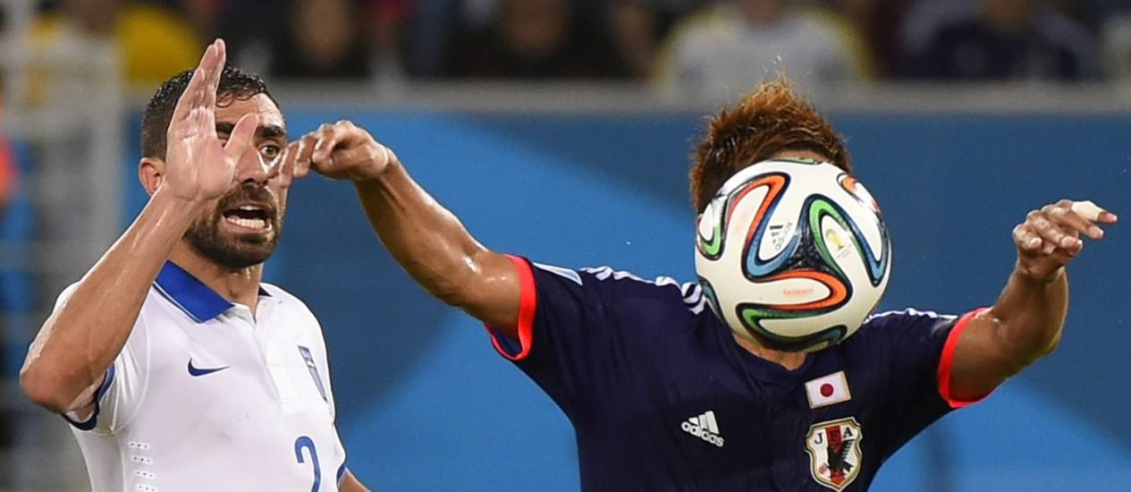 Atacante japonês Yoshito Okubo domina a bola, marcado pelo grego Giannis Maniatis Foto: FABRICE COFFRINI / AFP