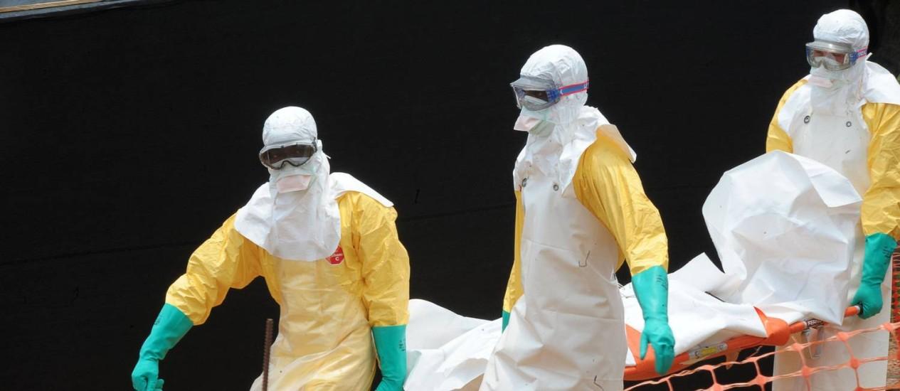 Médicos Sem Fronteiras carregam corpo de vítima de febre hemorrágica em consequência do vírus Ebola, na Guiné, em 1º de abril Foto: SEYLLOU / AFP