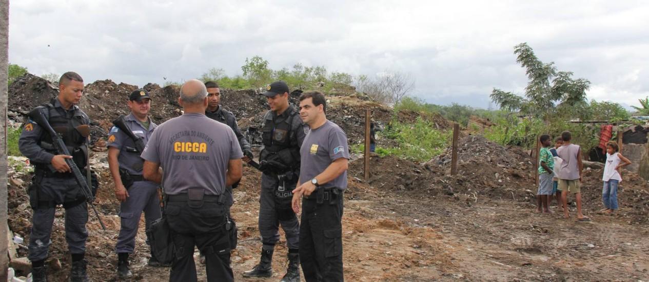 Coronel Padrone (à direita) com fiscais do Inea e PMs no lixão interditado em Caxias Foto: Paulo Araújo / Agência O GLOBO