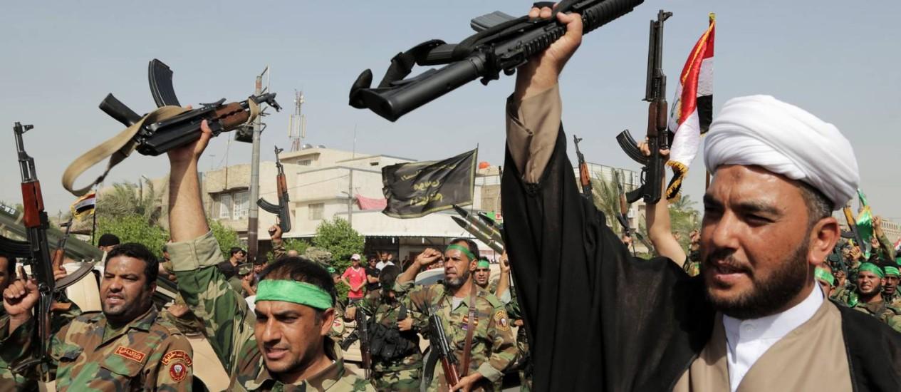 """Voluntários das recém-formadas """"brigadas de paz"""" levantam armas contra o Isis durante um desfile no reduto xiita de Cidade Sadr Foto: Khalid Mohammed / AP"""