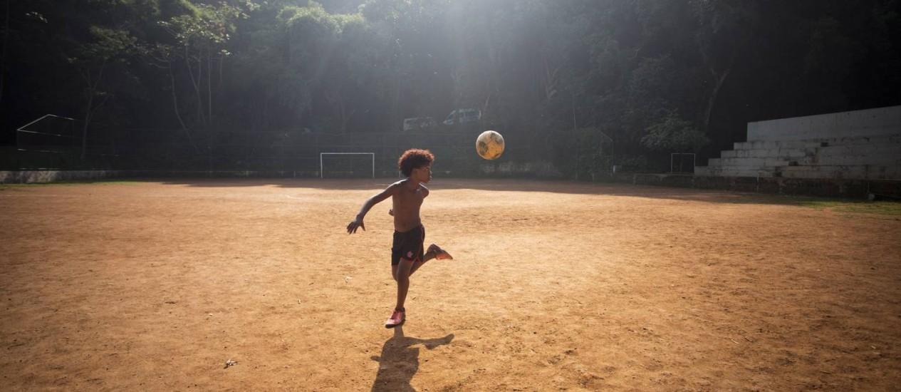 O menino se diverte mesmo sozinho batendo bola na quadra de terra da comunidade da Chácara do Céu, que resiste bravamente no Leblon Foto: Márcia Foletto / O Globo