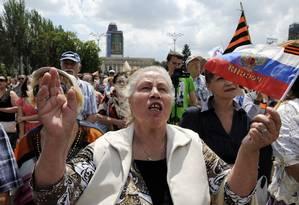 Mulher acena a militantes pró-Rússia na autoproclamada República Popular de Donetsk segurando uma bandeira russa Foto: AFP-22-6-2014