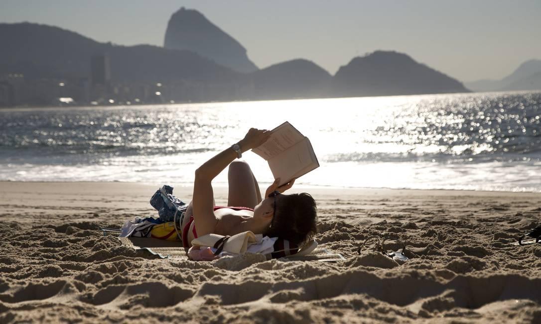 Mulher aproveita a manhã desta terça-feira para ler nas areias de Copacabana Foto: Márcia Foletto / Agência O Globo